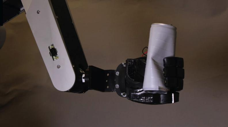 image of robotic arm crushing a can.